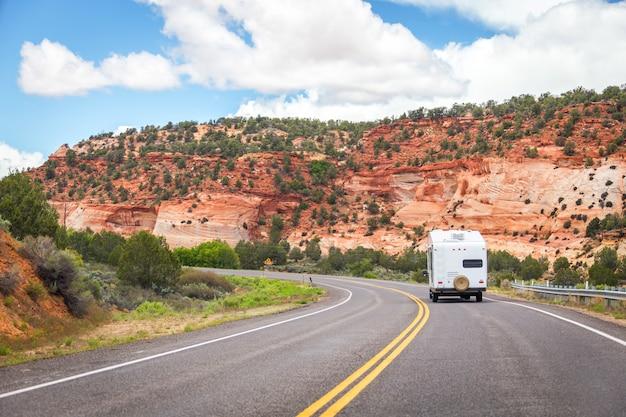 白い色のキャンピングカー車は山の背景を持つ道路に行く
