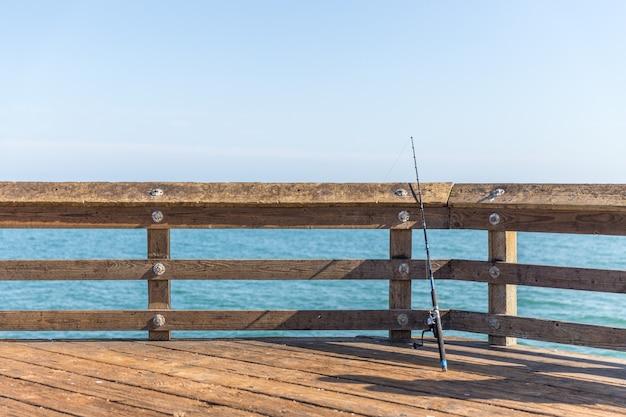 カリフォルニア州ベンチュラの桟橋のレールに寄りかかって釣り竿
