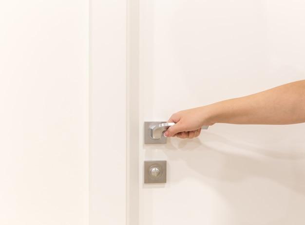 寝室の女性の手開きドア