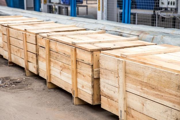 屋外に立っている多くの大きな木製貨物コンテナー