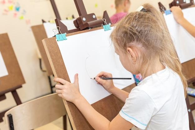 Малыш рисует изображение на мольберте в классе