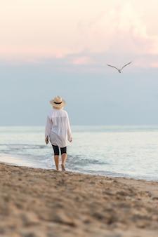 夕暮れ時のビーチを歩いて白いシャツと麦わら帽子を着ている女性