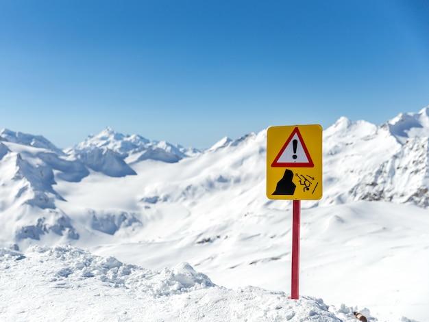 美しい山の風景の警告サイン。サインは落下のリスクについて警告します