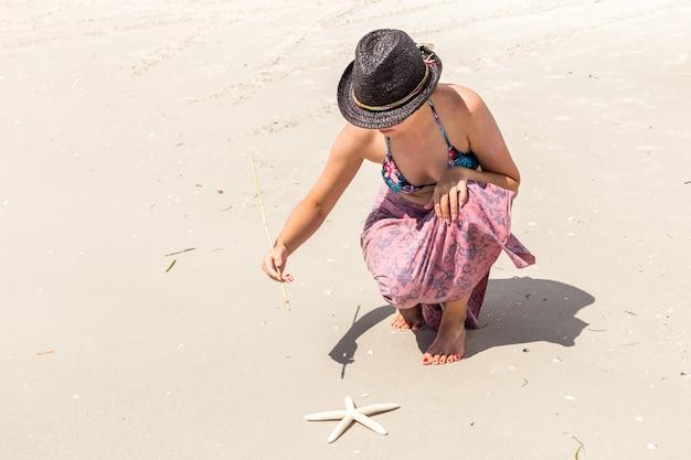 Женщина в черной шляпе, написание песчаного пляжа