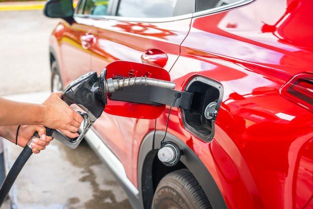燃料ピストルと赤い車を持つ女性