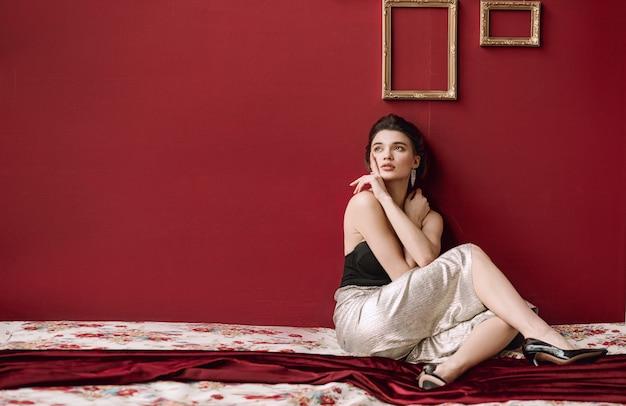 Красивая девушка сидит на кровати у красной стены