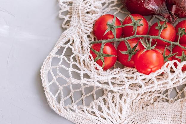 灰色の背景にメッシュバッグで枝トマトとタマネギ。