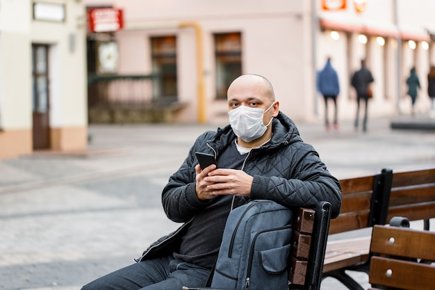 Человек, носящий защитную маску, держа смартфон.