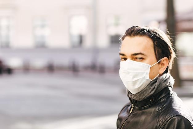 Человек в медицинской маске на лице, глядя в камеру.