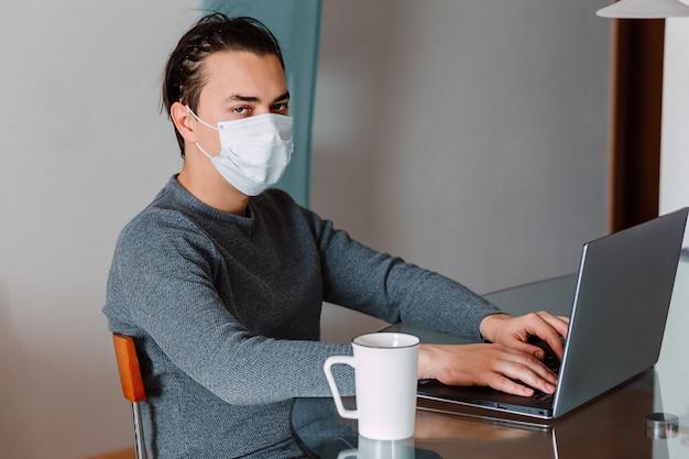 Парень работает дома с защитной маской на ноутбуке