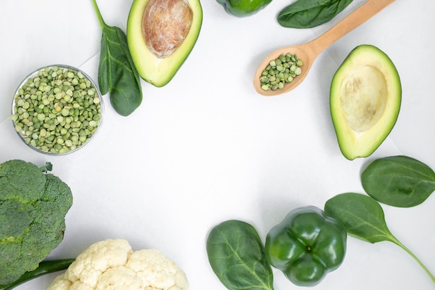 Зеленые овощи и травы на светлом фоне