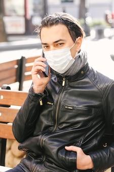 携帯電話を使用して保護フェイスマスクを持つ男