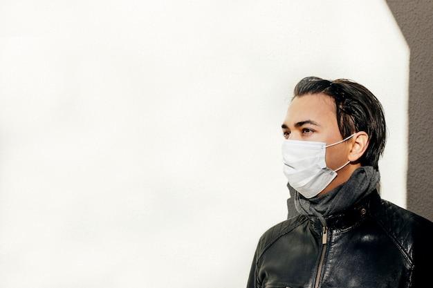 コロナウイルスの拡散に対する保護フェイスマスクを持つ男