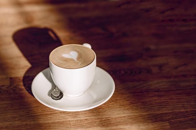 太陽の光の中でコーヒーカップ