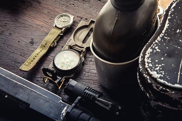 Военная тактическая экипировка для вылета. ассортимент снаряжения для выживания на деревянных фоне