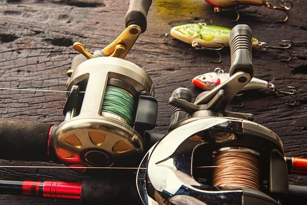 Рыболовные приманки, крючки и аксессуары на темном деревянном фоне