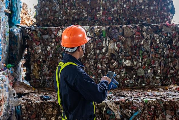 Портрет азиатских рабочих промышленного инженера с кучей пластиковых бутылок на заводе