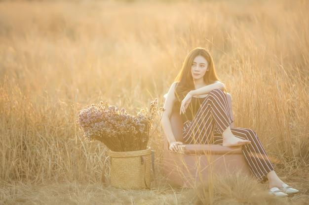 Красивая сексуальная молодая обнаженная женщина позирует в поле на закате