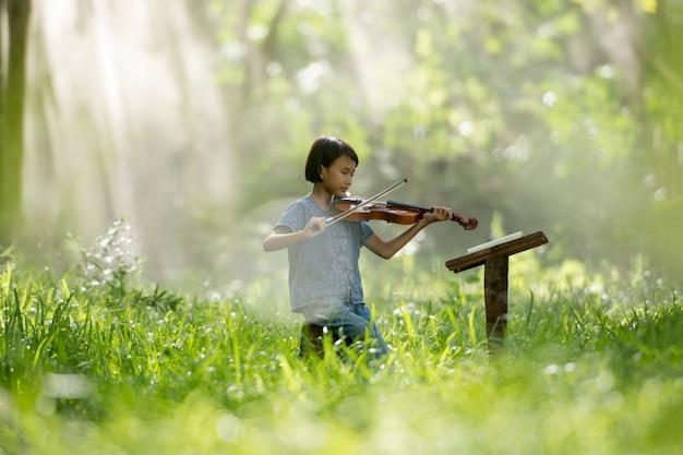 タイで勉強するバイオリンを弾く子供の女の子