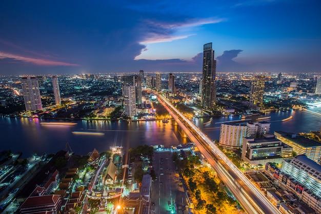 夕暮れ時のバンコクの交通機関、川沿いのモダンなビジネスビル(タイ)-パノラマ