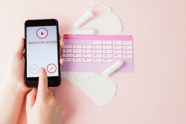 タンポン、女性用、生理用生理用ナプキン、女性用カレンダー、月経中のピンクの背景の痛み止め。月経周期と排卵の追跡