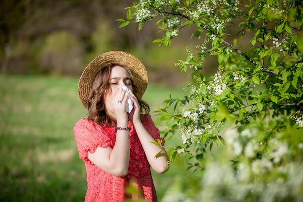若い女の子の鼻をかむと咲く木の前にティッシュでくしゃみ。人に影響を及ぼす季節性アレルゲン。美しい女性には鼻炎があります。