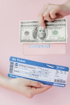 女性のパスポート、ドル、航空券はピンクの背景に手します。旅行の概念、コピースペース