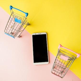 空白の画面の白い携帯電話とパステルピンクと黄色の背景にショッピングカート。最小限のスタイル、フラットレイ