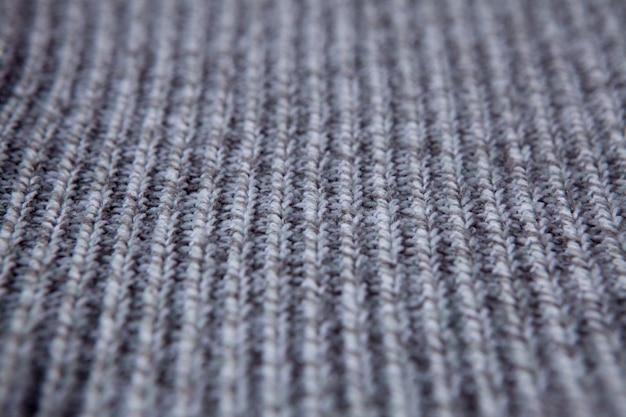 編み物のシームレスなパターン。灰色のウールの背景。古い手作りのニット