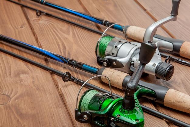 釣り道具-釣りの回転、フック、コピースペースを持つ木製の背景にルアー