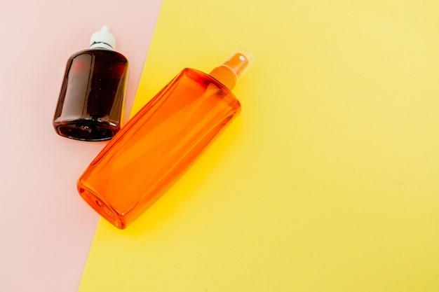 明るい正方形の黄色とピンクの背景にボトル日焼け止め。夏の海のリゾートのコンセプト。トップビュー、フラットレイアウト、ミニマリズム、コピースペース