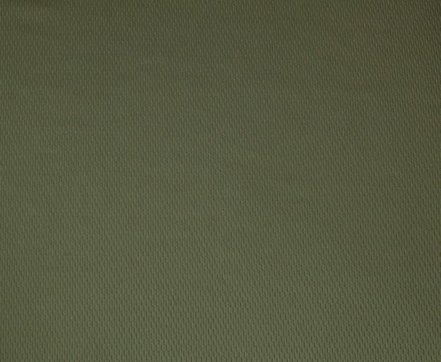 背景として暗い緑の粗いリネン生地のテクスチャのクローズアップ。