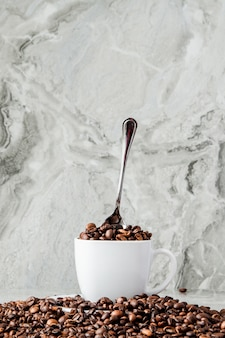 カップと大理石の背景にコーヒー豆のブラックコーヒー。