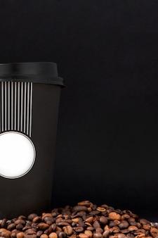 白いカップと黒い背景にコーヒー豆のブラックコーヒー。