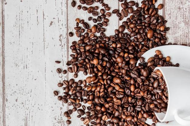 白いカップと明るい木製の背景にコーヒー豆のブラックコーヒー。