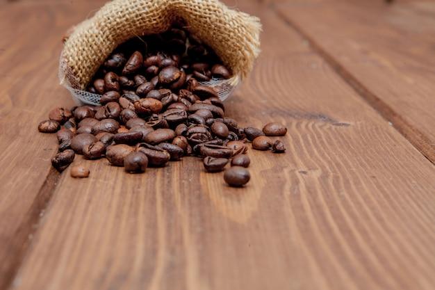 Свежие жареные кофейные зерна выпадают из мешка на деревянной поверхности. коричневые кофейные зерна, разбросанные из сумки на столе