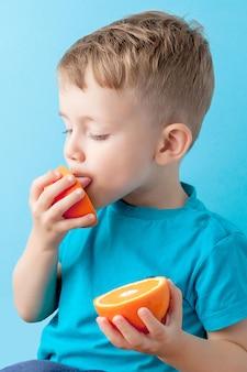 青色の背景、ダイエット、健康概念の運動に彼の手でオレンジを保持している小さな男の子