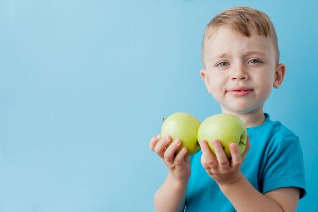 青色の背景、ダイエット、健康概念の運動に彼の手でリンゴを保持している小さな男の子