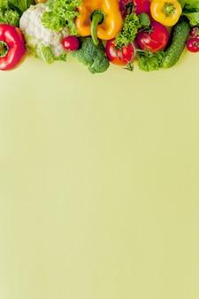 健康的なきれいな食事のレイアウト、ベジタリアン料理、ダイエット栄養の概念。黄色のテーブル背景、上面、フレーム、バナーのサラダの様々な新鮮な野菜の食材。