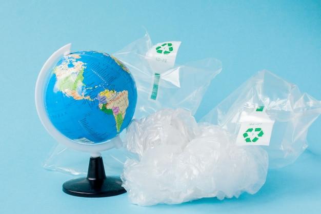 プラスチック汚染を禁止します。世界中のグローブとビニール袋。クリエイティブコンセプト