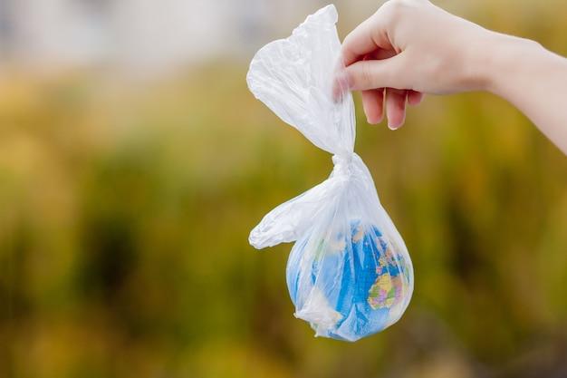 人間の手は、地球をビニール袋に入れて保持しています。プラスチック破片による汚染の概念。温室効果による地球温暖化。