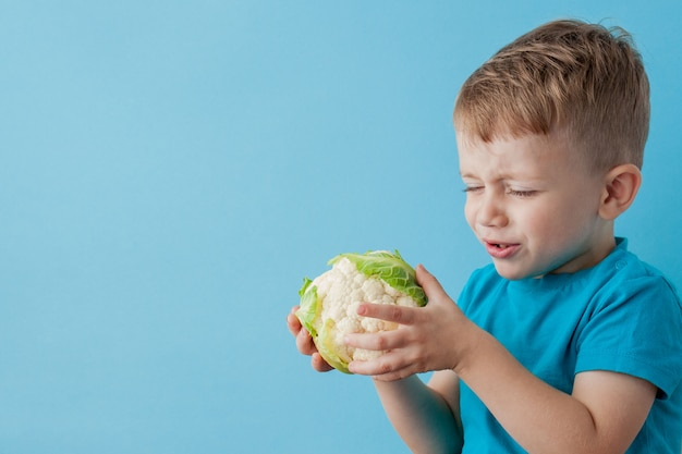 青色の背景、ダイエット、健康概念の運動に彼の手でブロッコリーを保持している小さな男の子