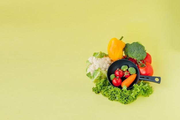 自然食品。ブロッコリー、レタス、赤と黄色のピーマン、黒のフライパンにキュウリと野菜。上面図。ビーガンと健康の概念。