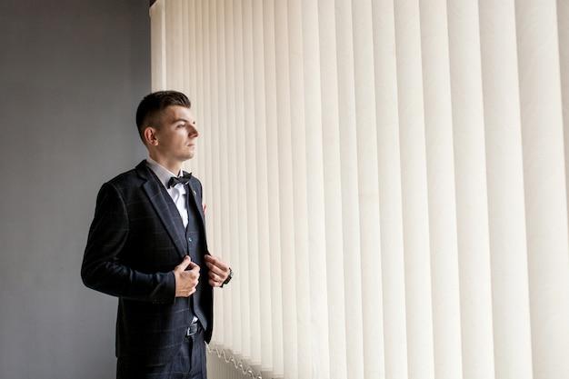 男は彼のビジネスシャツを着ることで仕事の準備をします。結婚式前の新郎の朝の準備