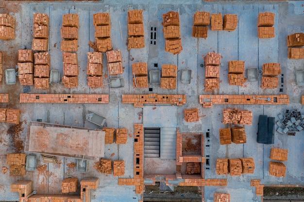 建築用に保存された粘土レンガのパレット。建設現場の背景。トップビュー、産業の背景