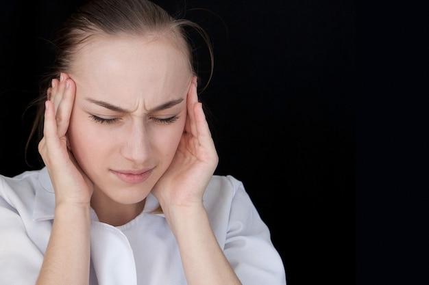 Вид спереди молодого интеллектуального доктора на черной предпосылке с космосом текста. у медицинского работника болит голова