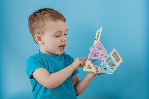 Мальчик просматривает фигуру в конструкторе цвета с подключением магнитов