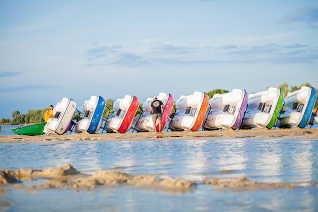 Штабелированные катамараны на озере. яркие красочные водные велосипеды на берегу озера