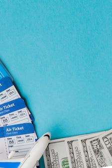 青色の背景にパスポート、ドル、飛行機、航空券。旅行の概念、コピースペース