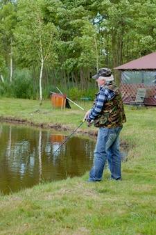 漁師は湖でサーモンフライフィッシングをキャッチします。